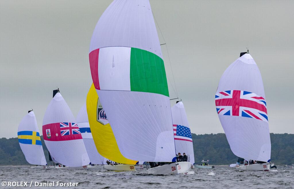 Fleet sailing downwind with kites, Italian boat leading fleet.