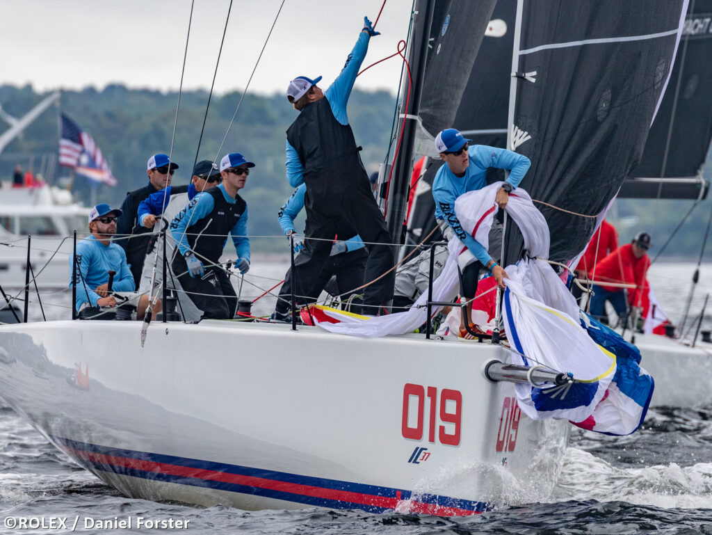 New York Yacht Club sailing downwind. Bow team are hoisting the spinnaker.