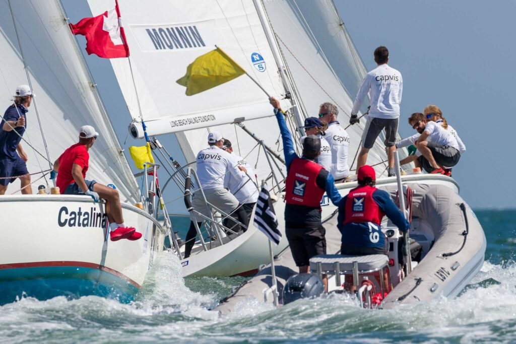 Umpires holding a flag up, while following two boats sailing in a line.