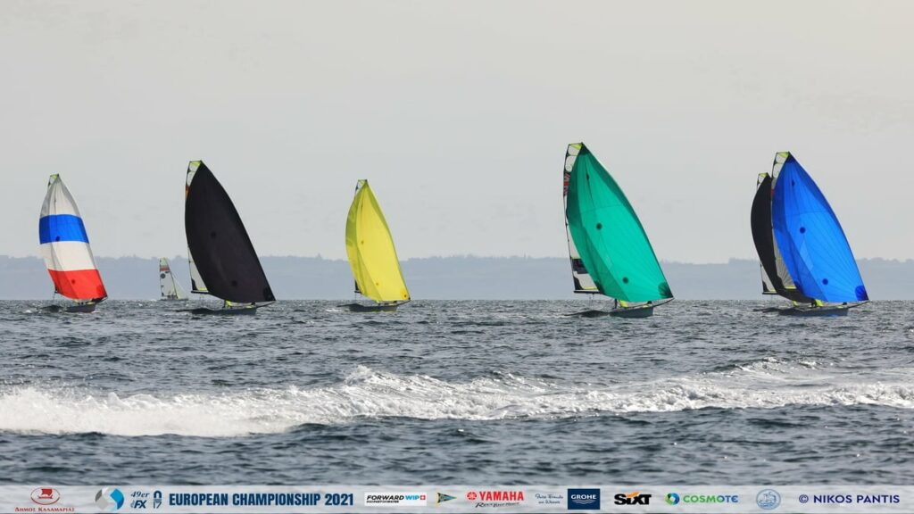 49er fleet sailing on a spinnaker reach. Wake of a RIB in front of them.