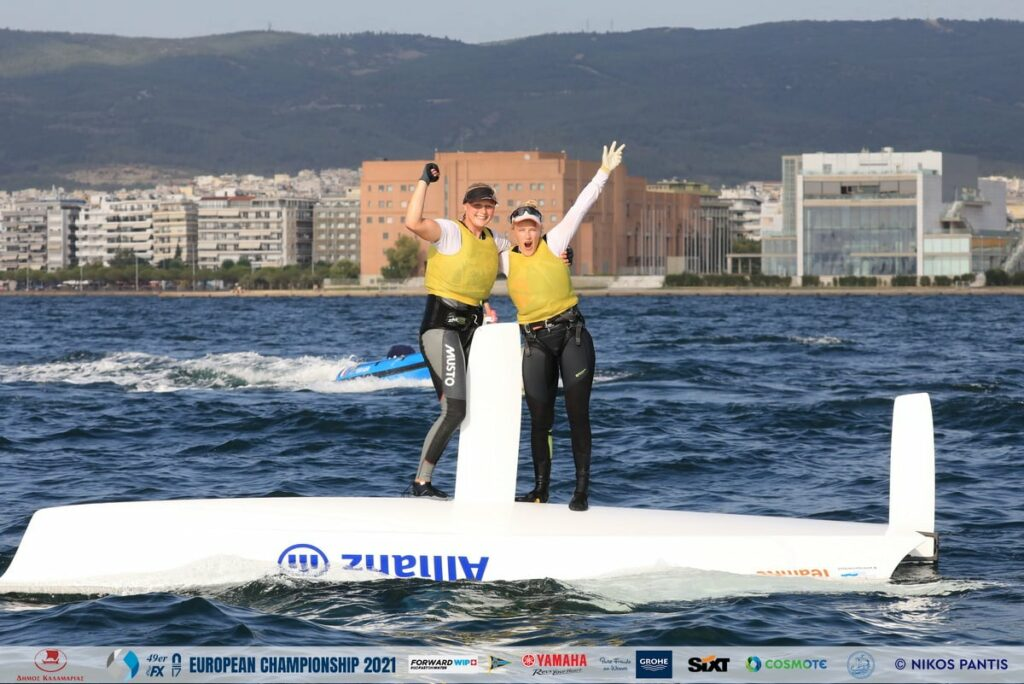 Odile van Aanholt and Elise de Ruyter celebrating on top of their capsized boat.