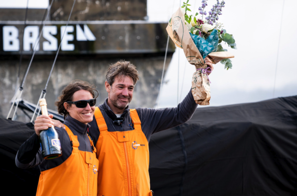 Fisher and Mettraux with flowers and champagne on the dock following the race.