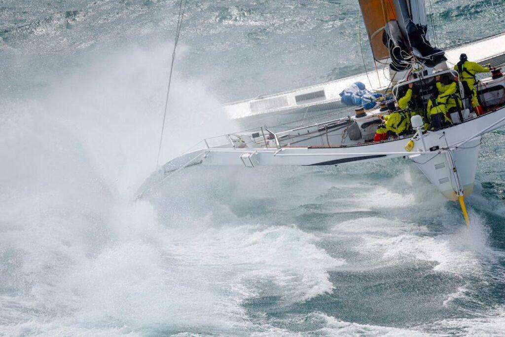 Behind Argo sailing upwind, creating massive wash.