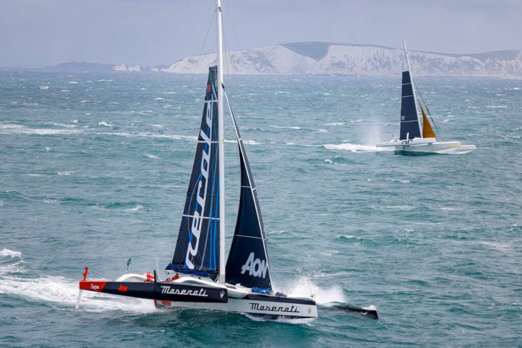 Aerial shot of two multihulls racing in white-capping conditions.