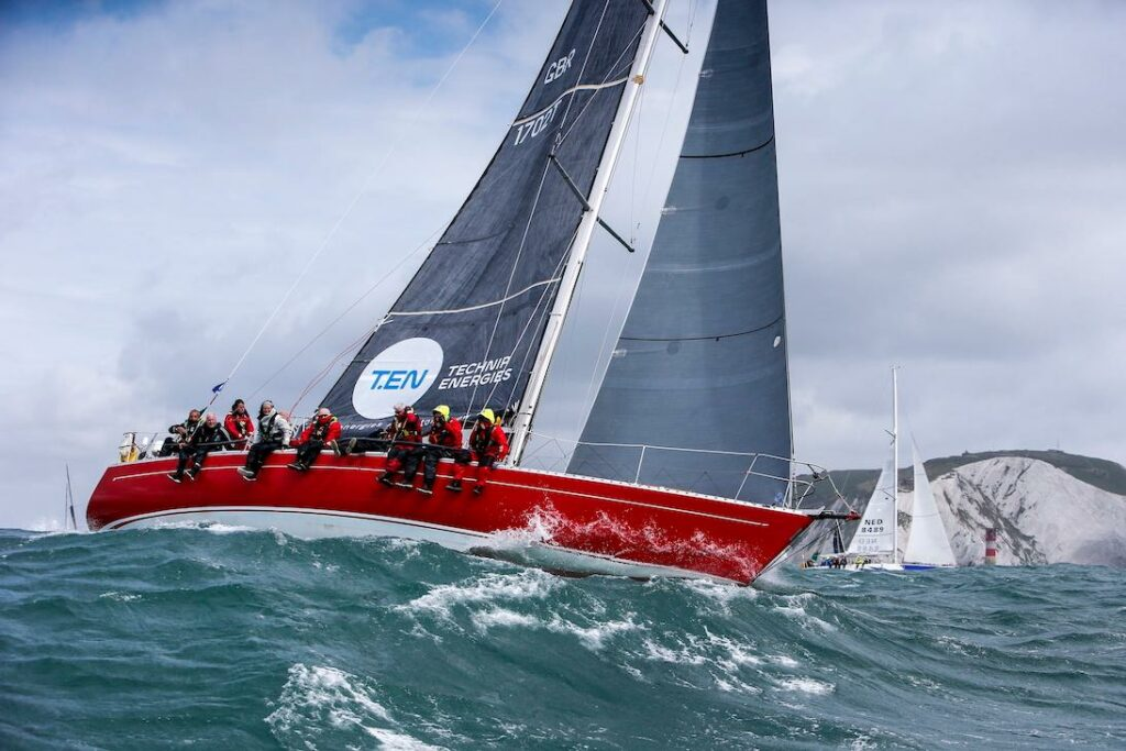 The red hull of Scarlet Oyster surfing a wave while sailing upwind with land and another yacht in the background.