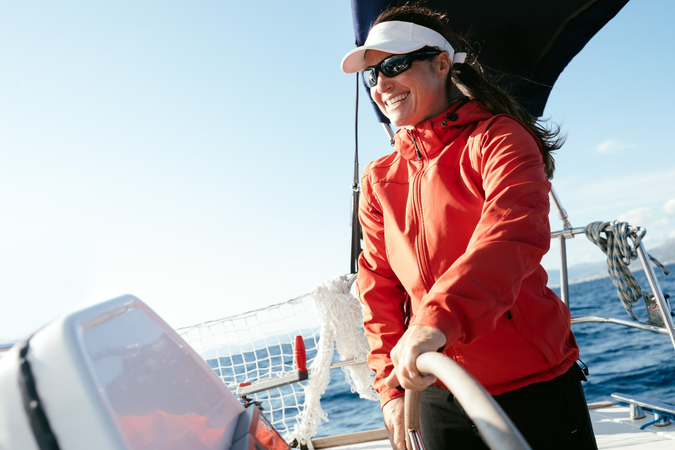 A woman steering a yacht, a rolled up bimini above her.