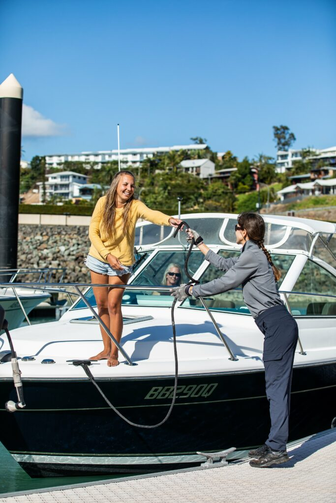 A powerboat docking, a woman on the bow passing a dock like to a woman on the dock.