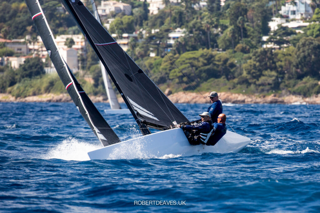A 5.5 metre sailing upwind creating splash, crew leaning right over the side.