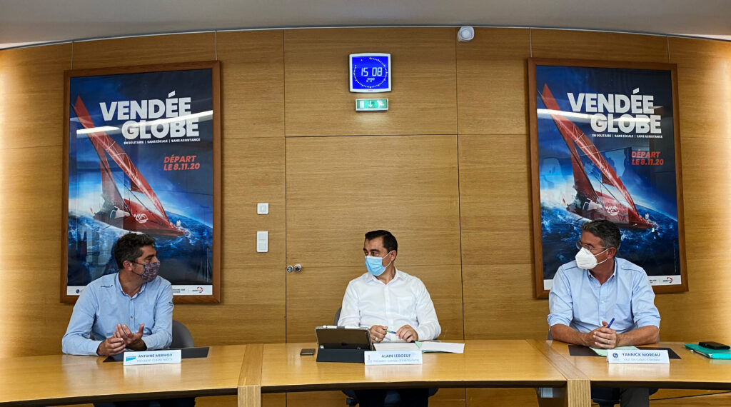 Antoine Mermod, Alain Leboeuf, Yannick Moreau at theVendée Arctique - Les Sables d'Olonne presentation. Sitting at a table, masks on. Vendée Globe poster is behind them.