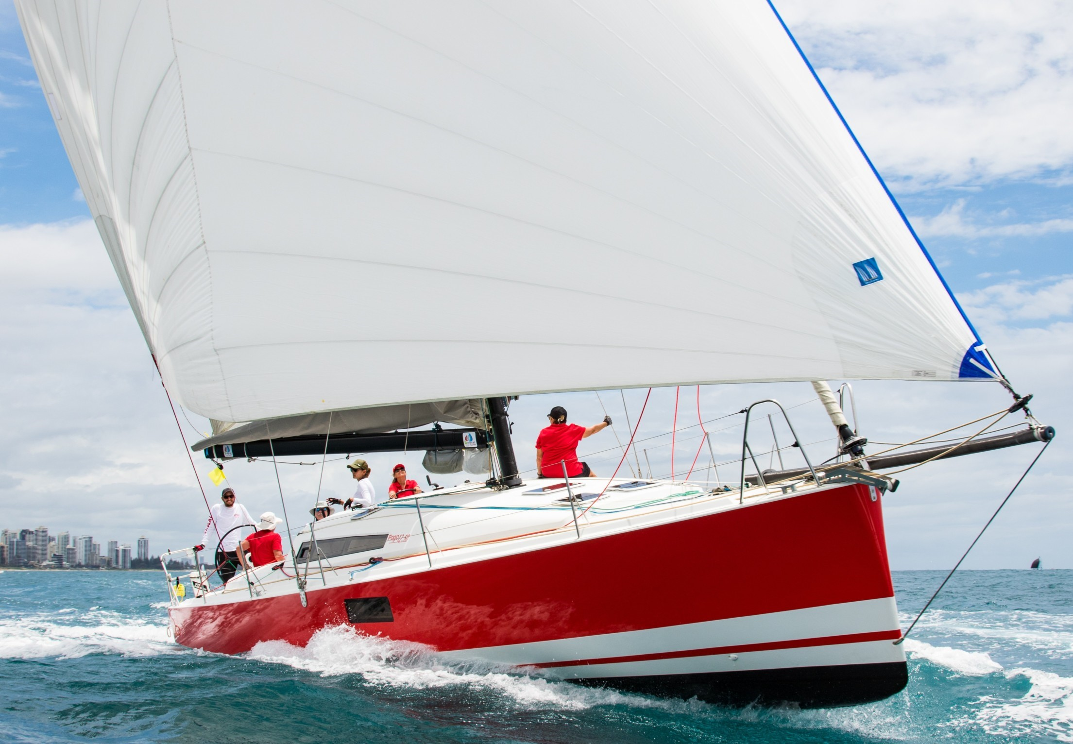 Red yacht on a spinnaker reach, relatively flat waters, creating a little wash.