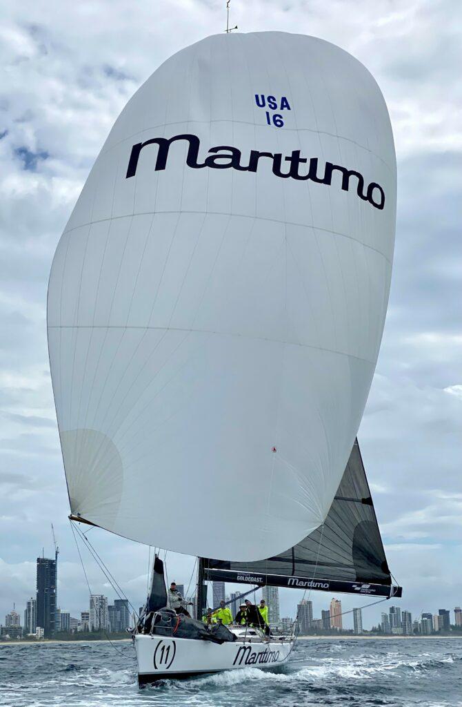 Maritimo sailing on a kite run (white kite), high rise buildings behind them.