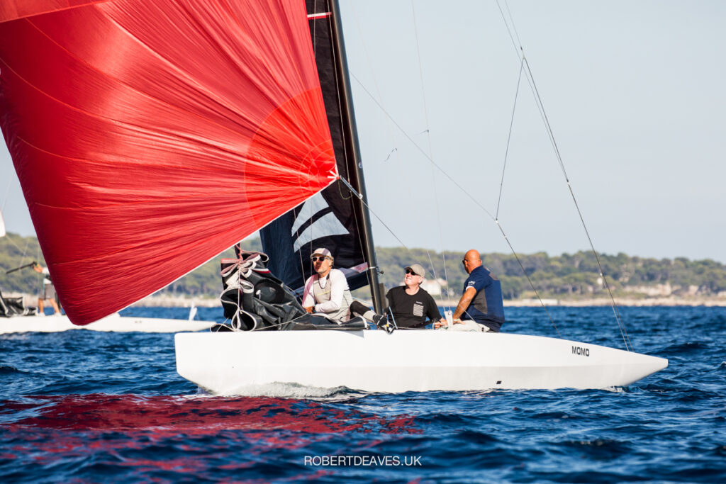 Momo sailing downwind with red kite, bowperson sitting near the front.