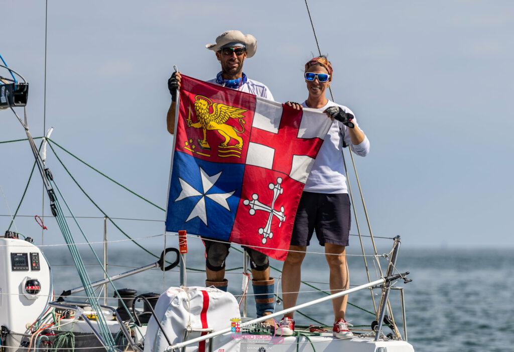 Giovanna Walchechi e Andrea Pendibeen tengono la bandiera sulla loro barca dopo il completamento.