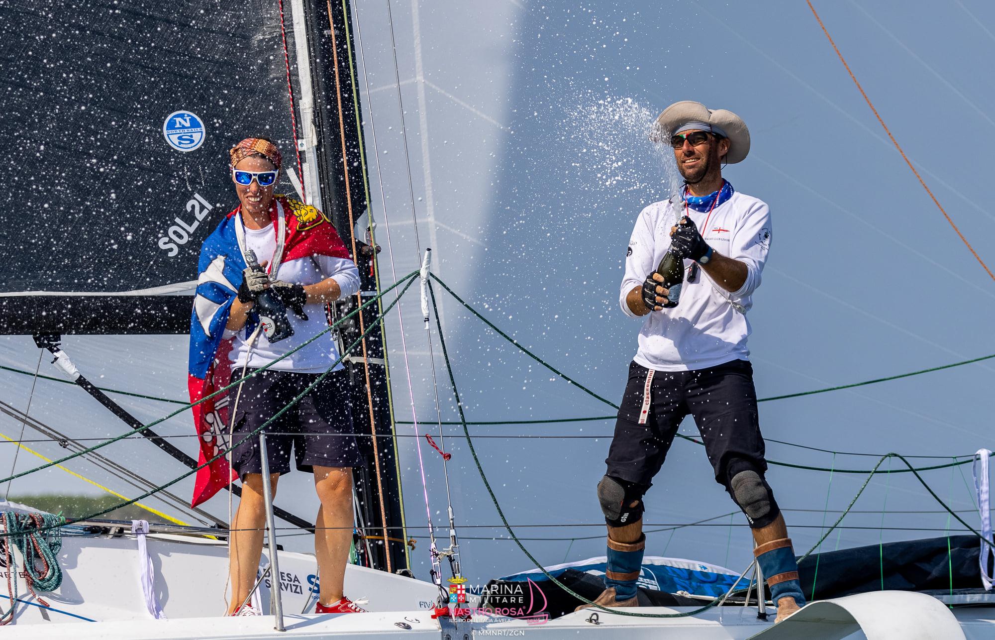 Giovanna Valsecchi & Andrea Pendibene showering champagne on their boat.