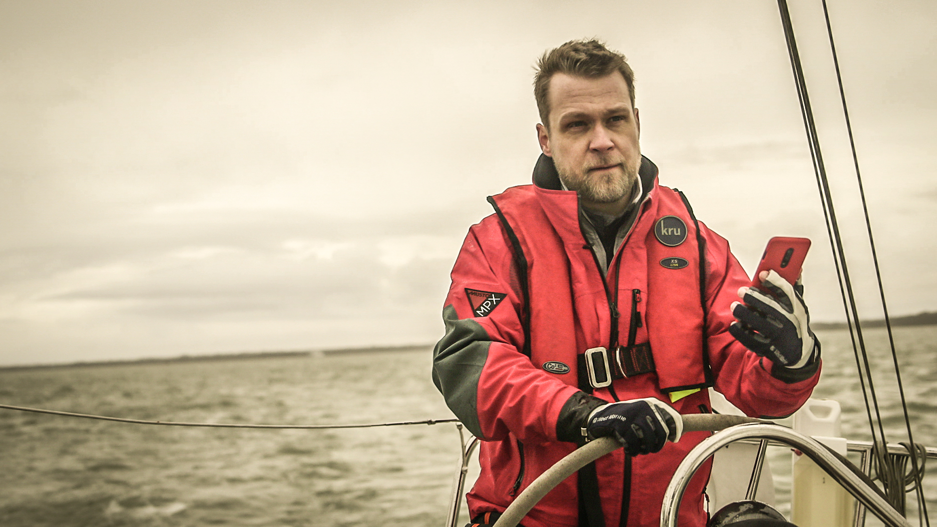 Jelte Liebrand steering a boat, holding a phone (using savvy navvy).