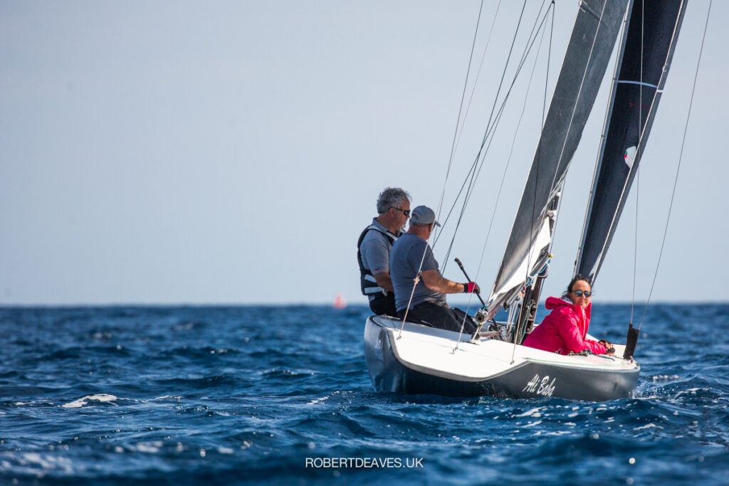 The stern of Ali Baba as they sail upwind. A crew member smiling back at the camera.