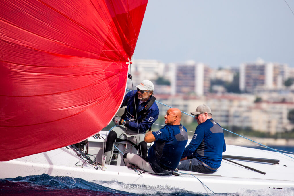 Momo sailing downwind with red kite, crew concentrating and trimming the kite.