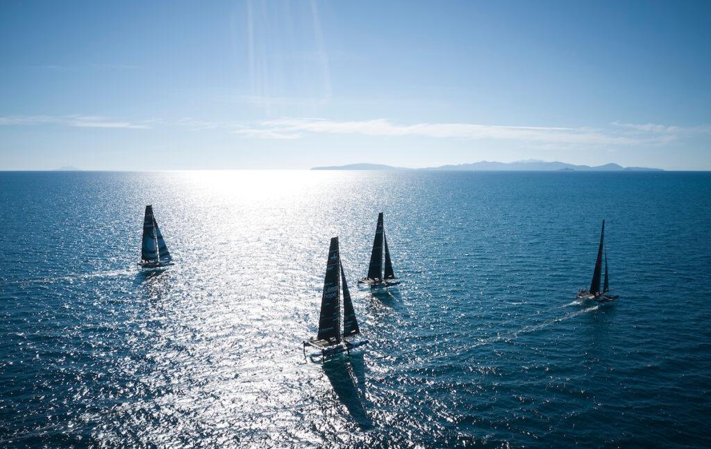 Aerial shot of fleet sailing upwind, sun glistening on the water.