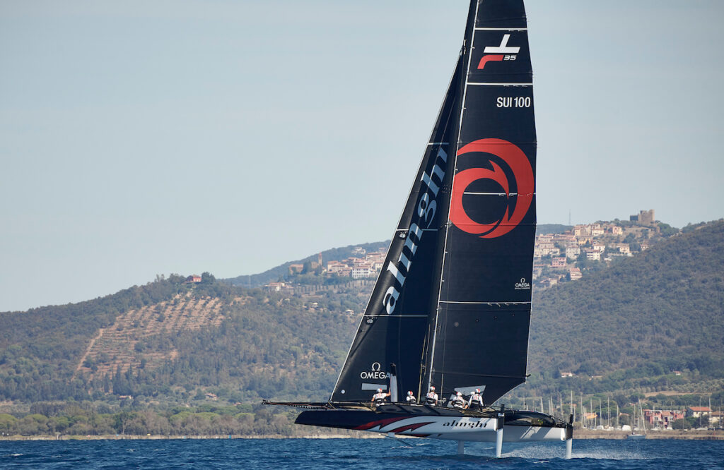 Alinghi sailing upwind, mountains and buildings in the background.