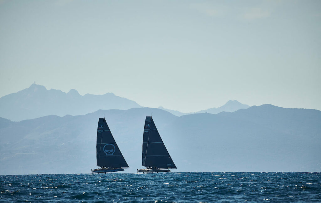 Zoulou and another boat sailing in a line, mountains in the backgrou.d
