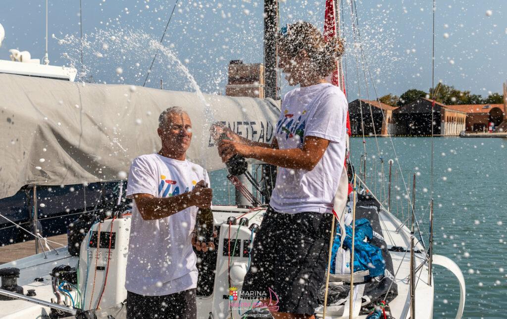 Claudia Rossi e Pietro Dalì spruzzano champagne sulla barca al molo.