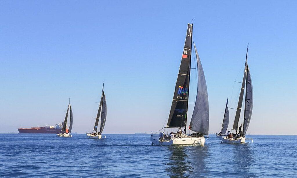Cinque barche viaggiano su acque piatte, a portata di mano.