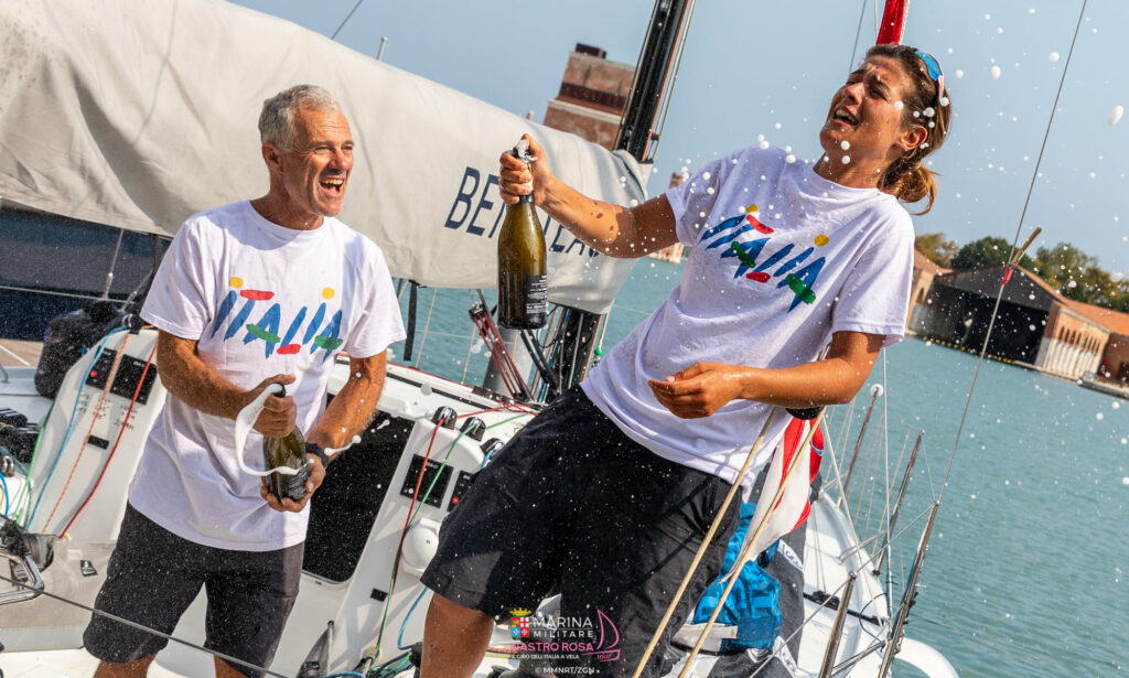 Claudia Rossi and Pietro D'Alì about to pop champagne on their boat on the dock.