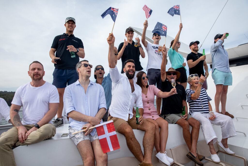 Group of people on a boat waving flags, having champagne.