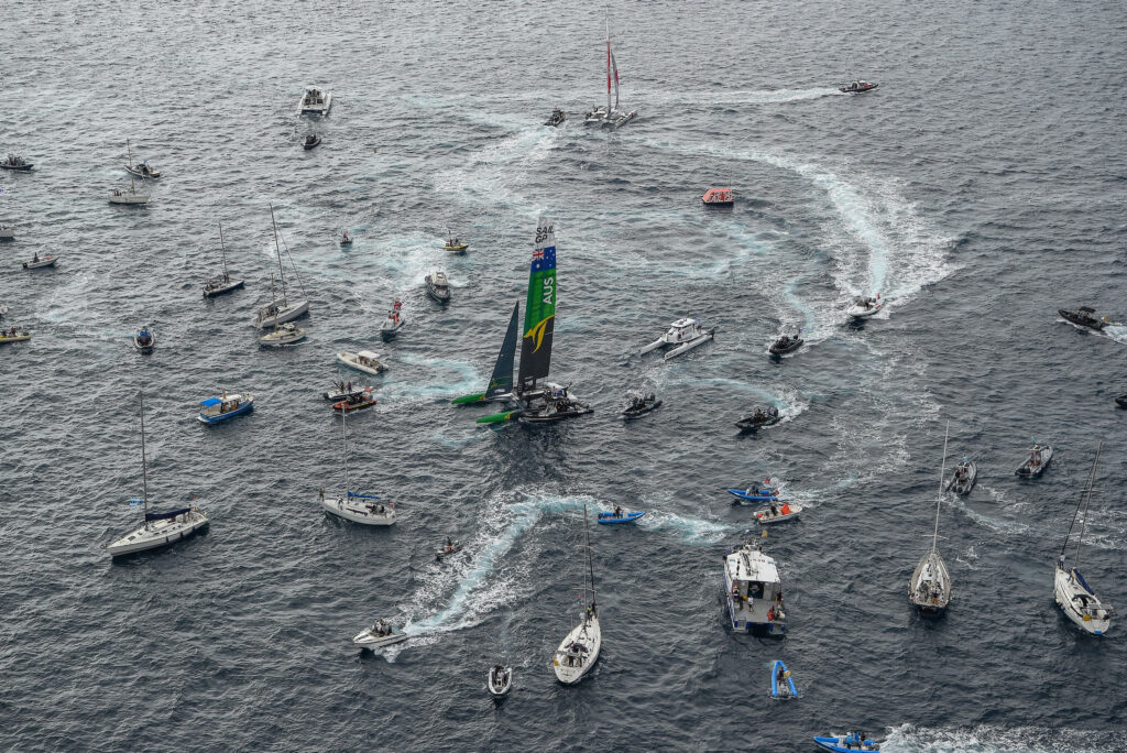 Aerial shot of the Australian SailGP boat surrounded by heaps of spectator boats.