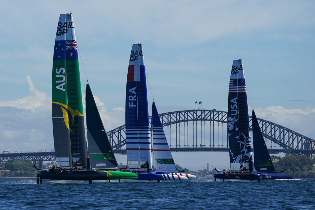 Three SailGP F50s sailing with the harbour bridge in the background.