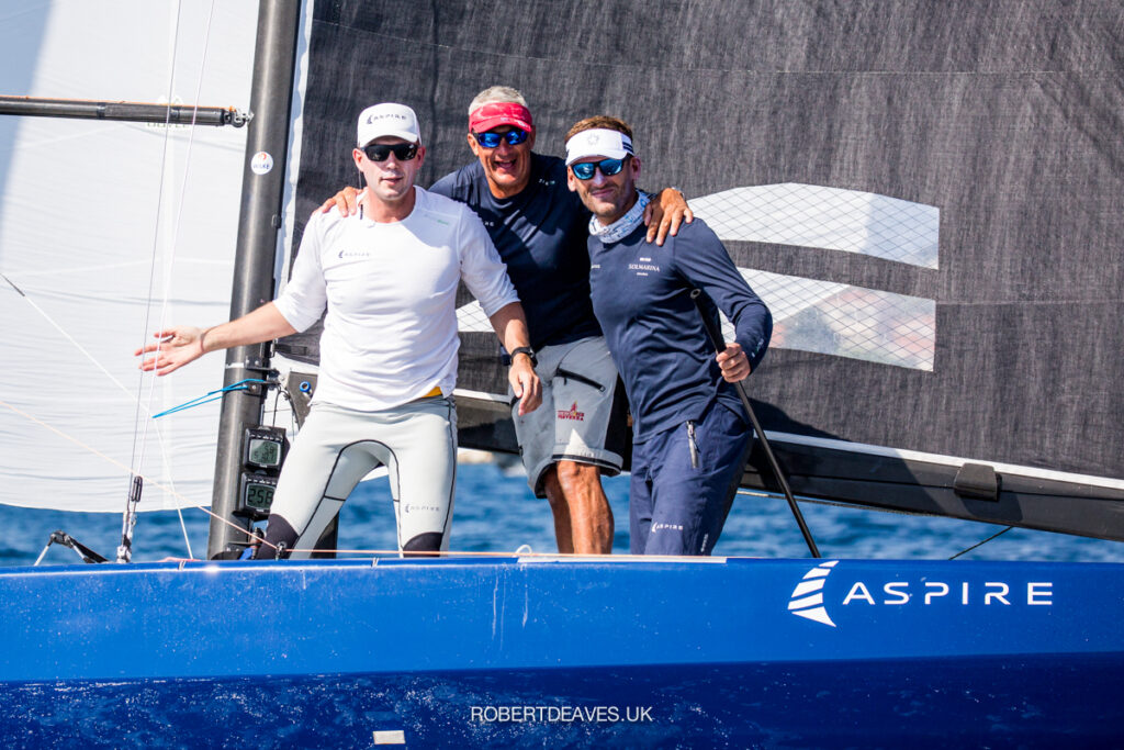 Aspire crew standing, smiling at camera on their blue hulled boat.
