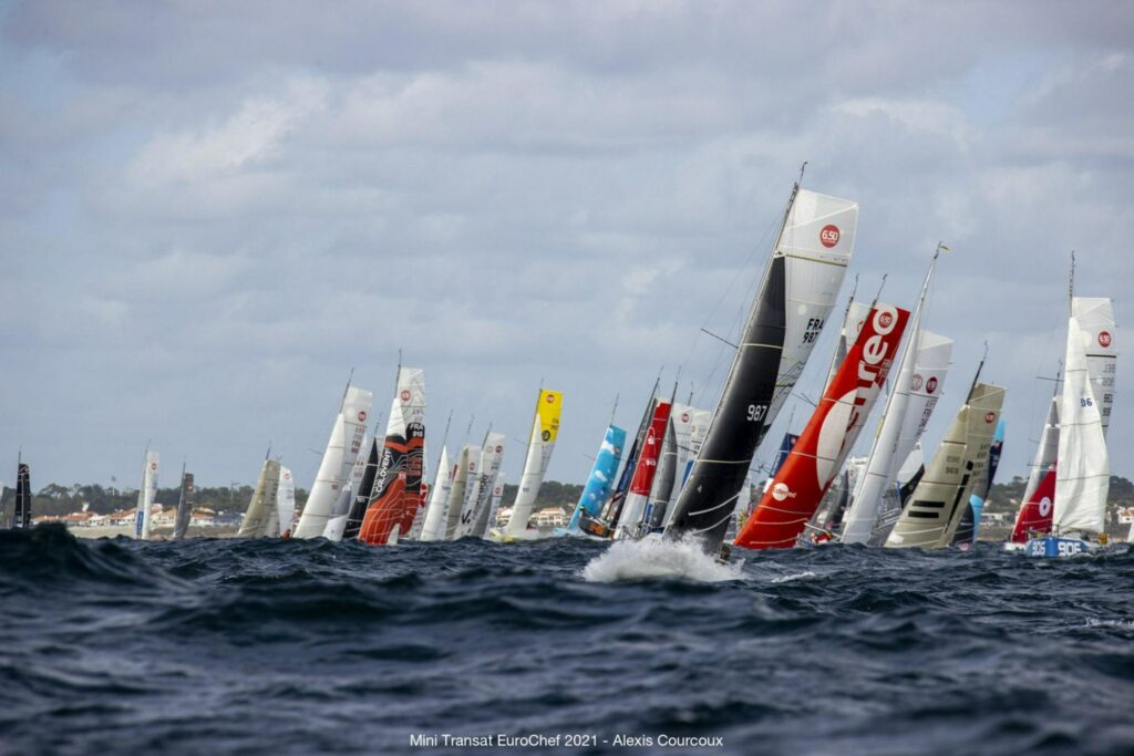 Fleet sailing towards the camera in choppy conditions.