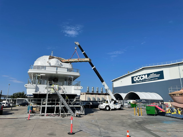 60-metre motor yacht, OCEANA, on a hard stand, a crane lifting something onto the top deck.