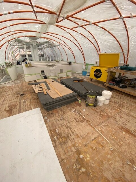 The inside of 60-metre motor yacht, wooden floor (not finished) pieces of wood and equipment everywhere. Plastic roof for construction.