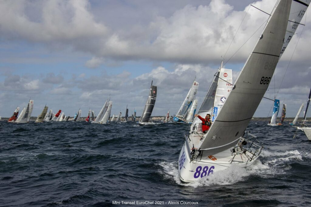 A competitor sailing upwind to the camera, fleet behind him on different tacks.