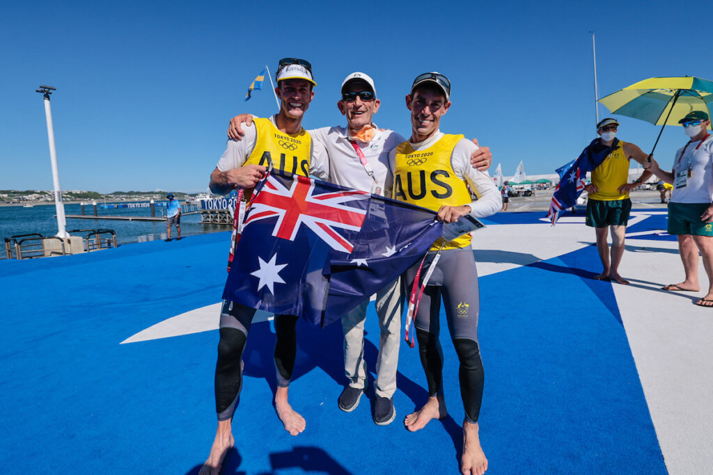 Will Ryan (left), Victor Kovalenko (centre) and Mat Belcher (right) on land in their sailing gear, smiling.