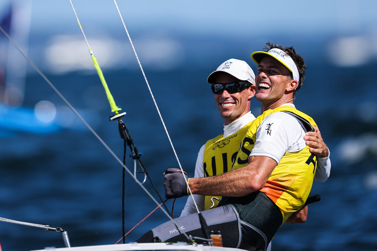 Mat Belcher and Will Ryan smiling and patting each other after finishing the Medal Race.