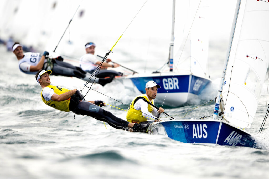 Mat Belcher and Will Ryan sailing upwind through chop, with GBR behind them.