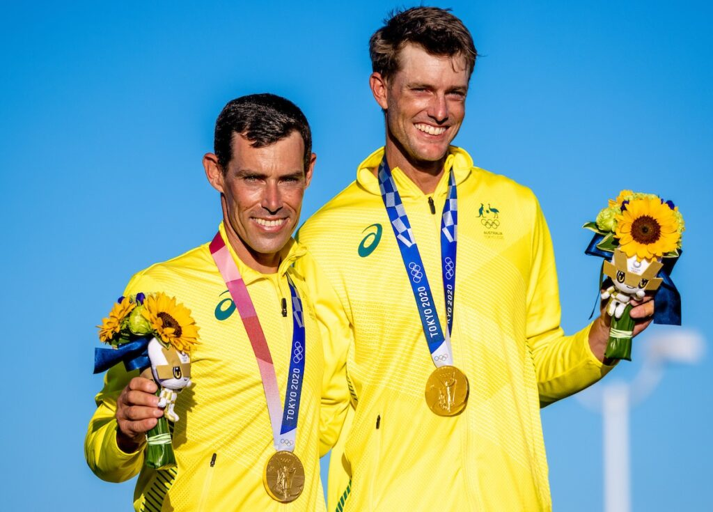 Mat Belcher and Will Ryan smiling at the medal ceremony with their medals around their necks and holding flowers.