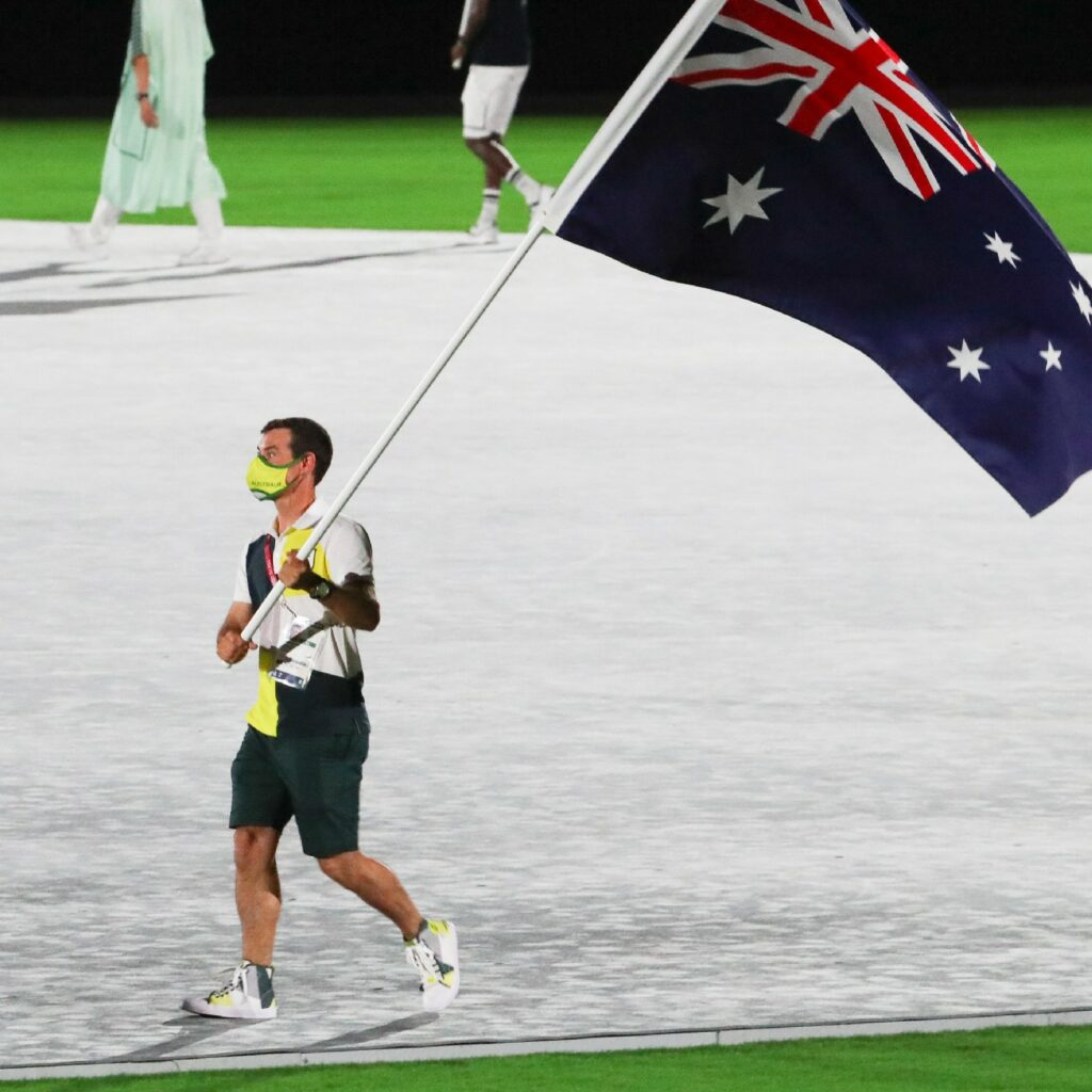 Mat Belcher holding the Australian flag at the Closing Ceremony.