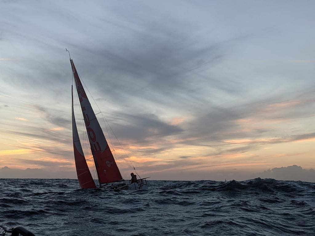 Boat sailing in big swells as sunset.