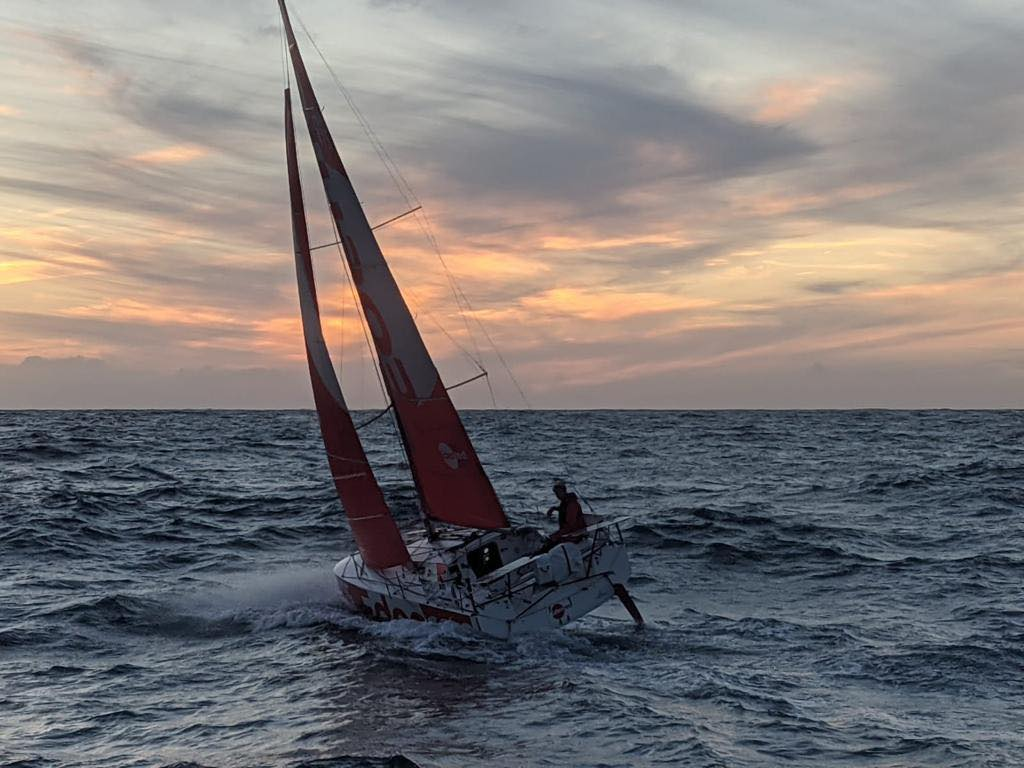 Basile Bourgnon sailing upwind, creating a little bit of splash, during sunset.