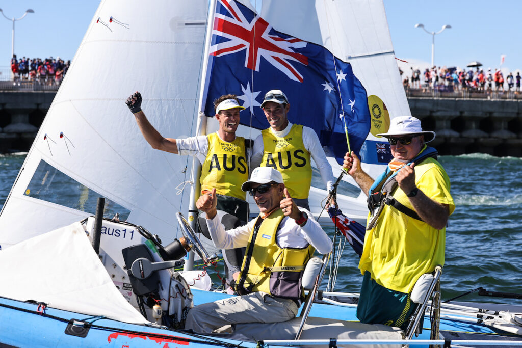 Mat Belcher, Will Ryan, Victor Kovalenko and Iain Murray on the water smiling at the camera following 470 Tokyo 2020 Medal Race