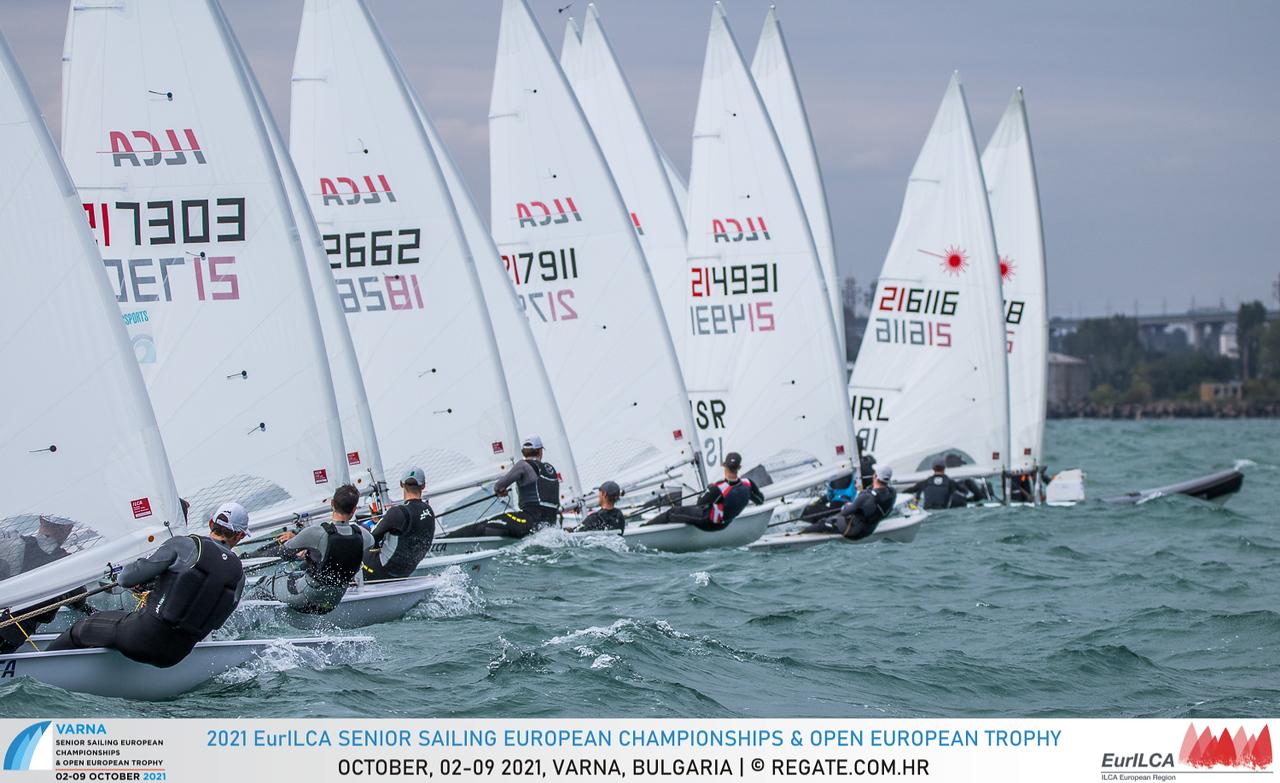Laser fleet sailing upwind after the start line.