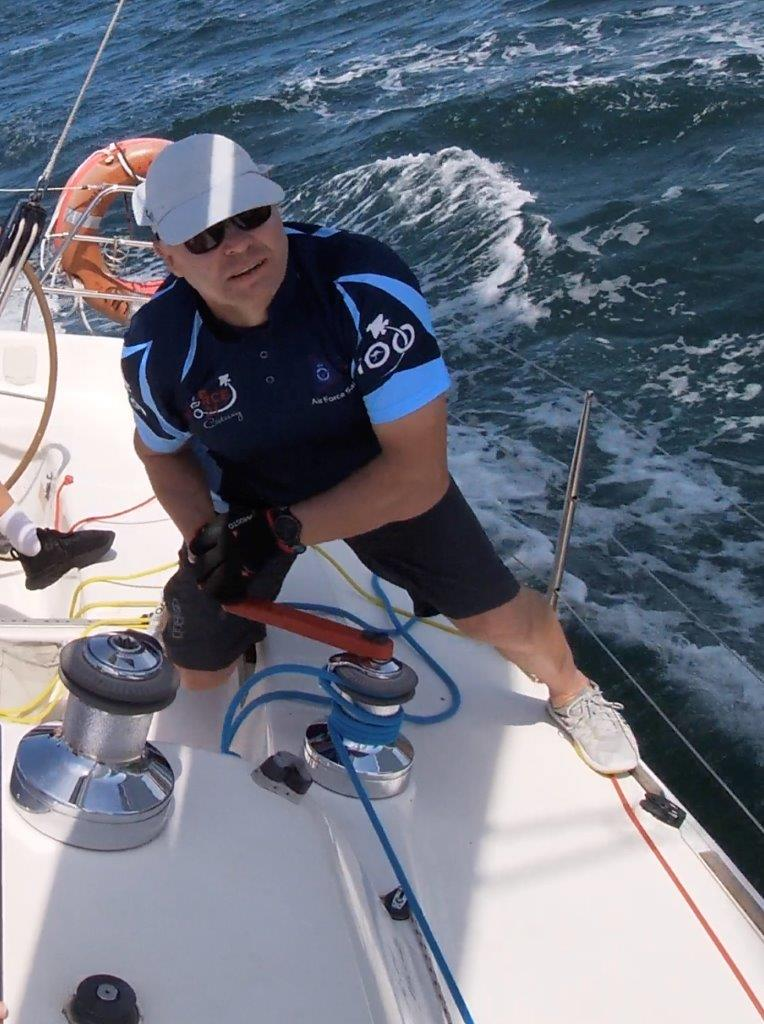 Darrell Greig winding a winch while sailing.