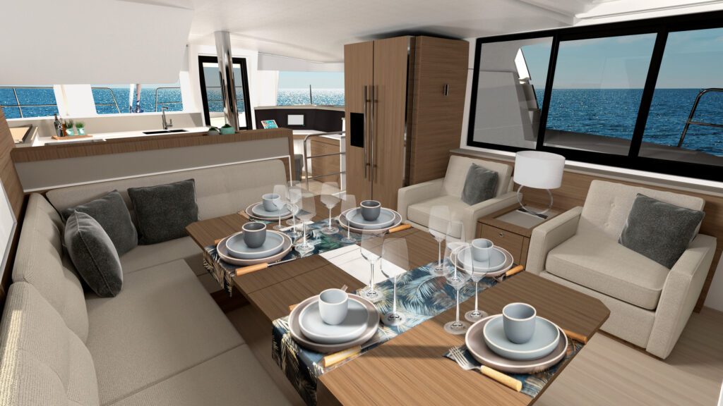 Interior of Bali 4.4. Living room table surrounded by windows looking onto the water.