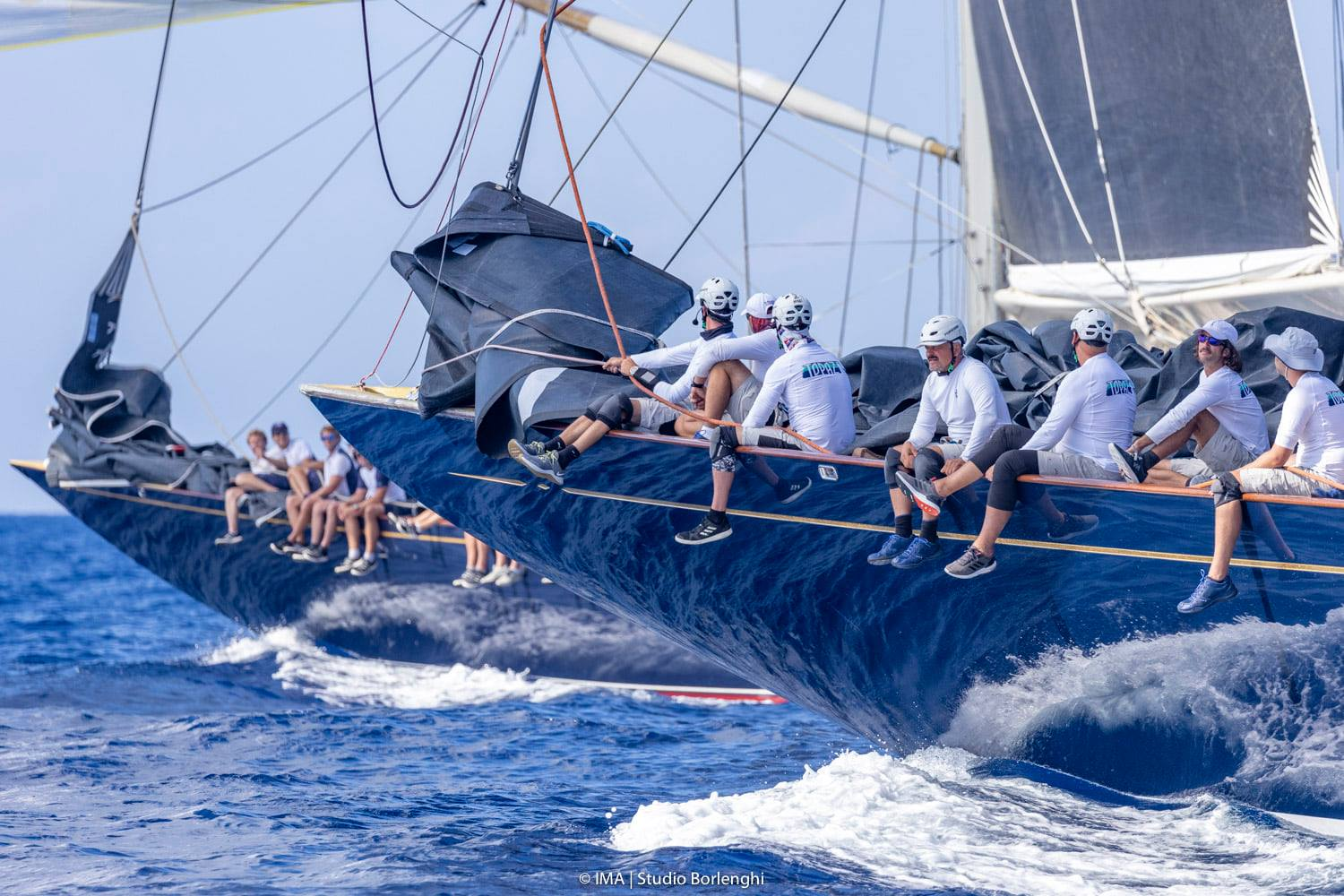 Topaz and Velsheda side by side downwind. Crew sitting on the side.