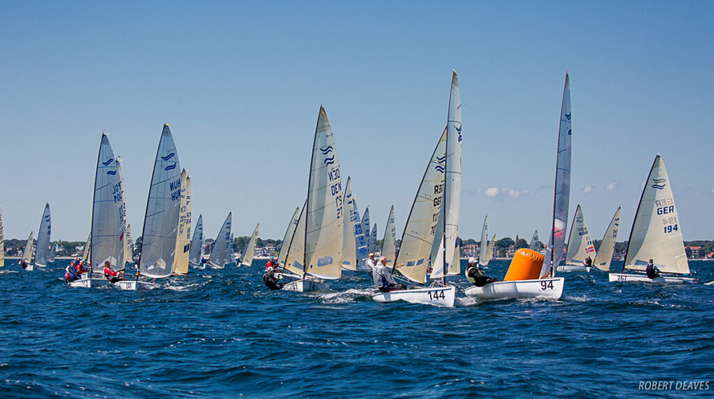 Finn fleet sailing downwind/reach, a couple of the boats are passing an orange mark.