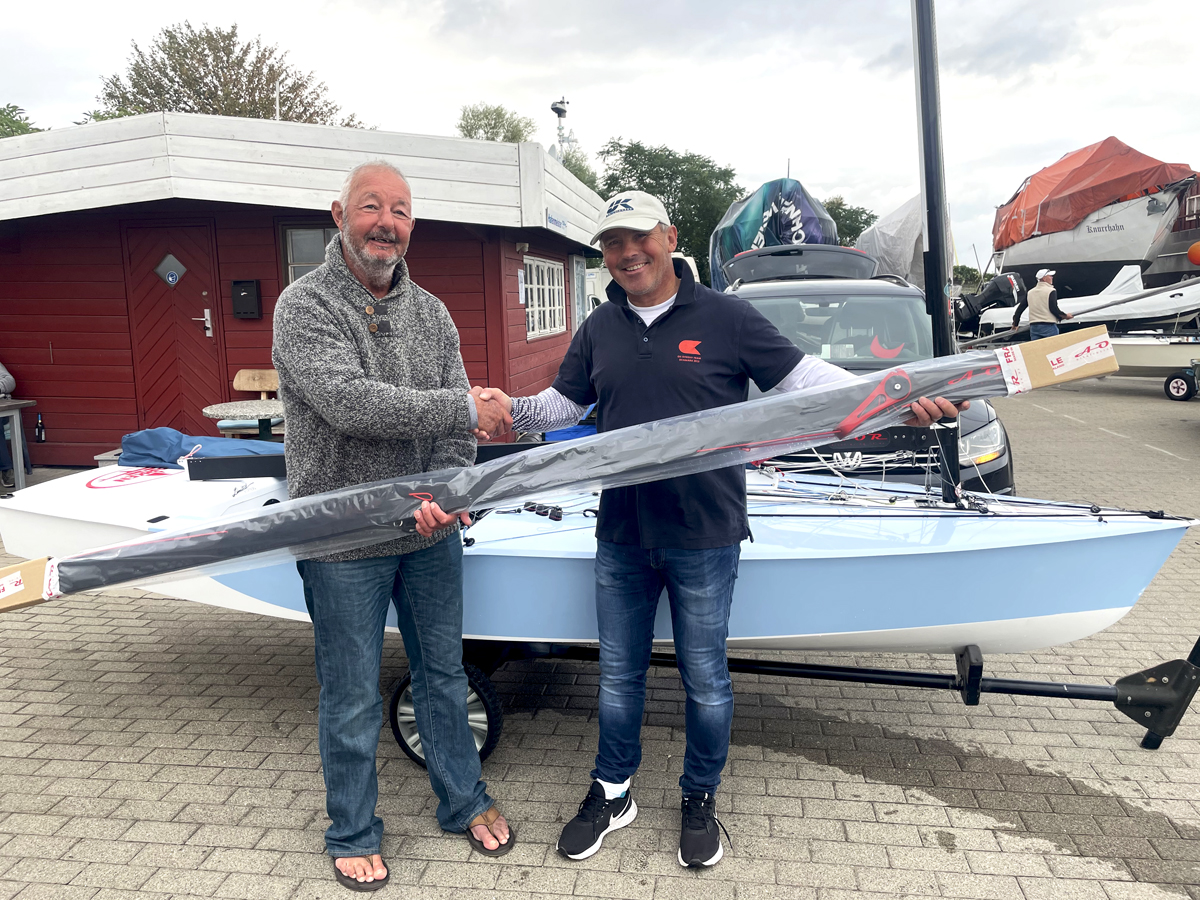 Bo Petersen and Greg Wilcox shaking hands while holding a boom on land in front of a blue OK Dinghy.