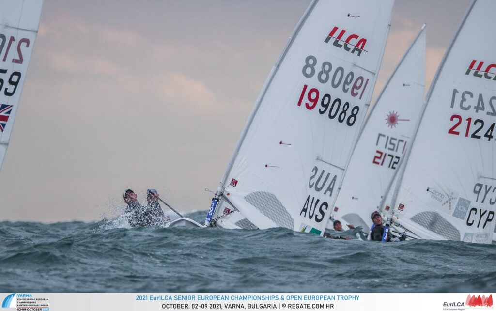 A sailor sailing on a range and coming up a big wave with a couple of sailors behind them.